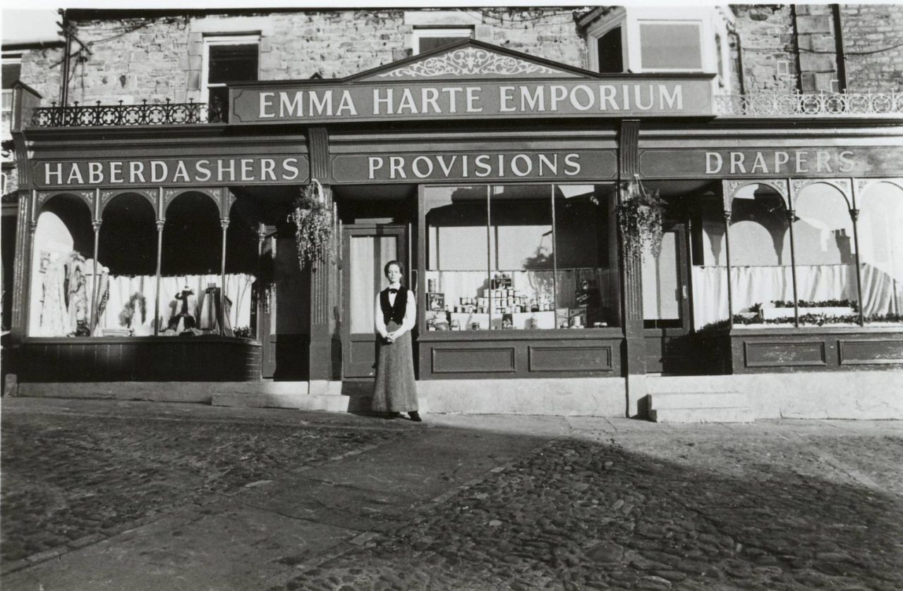 An older Emma Harte (Deborah Kerr) stares at the photo of her younger self (Jenny Seagrove) in front of her first store, Emma Harte's Emporium - from the miniseries of A Woman Of Substance. — with Deborah Kerr and Jenny Seagrove.